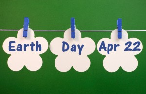 Earth Day, April 22, message greeting written across white flower cards hanging from pegs on a line against an environment friendly green background.